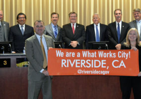 Mayor Rusty Bailey and Chief Innovation Officer Lea Deesing in frontground; Riverside City Council with What Works Cities banner